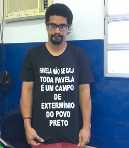 "André Constantine displays shirt that says ""Favela don't be quiet. Every favela is an extermination camp for black people."""