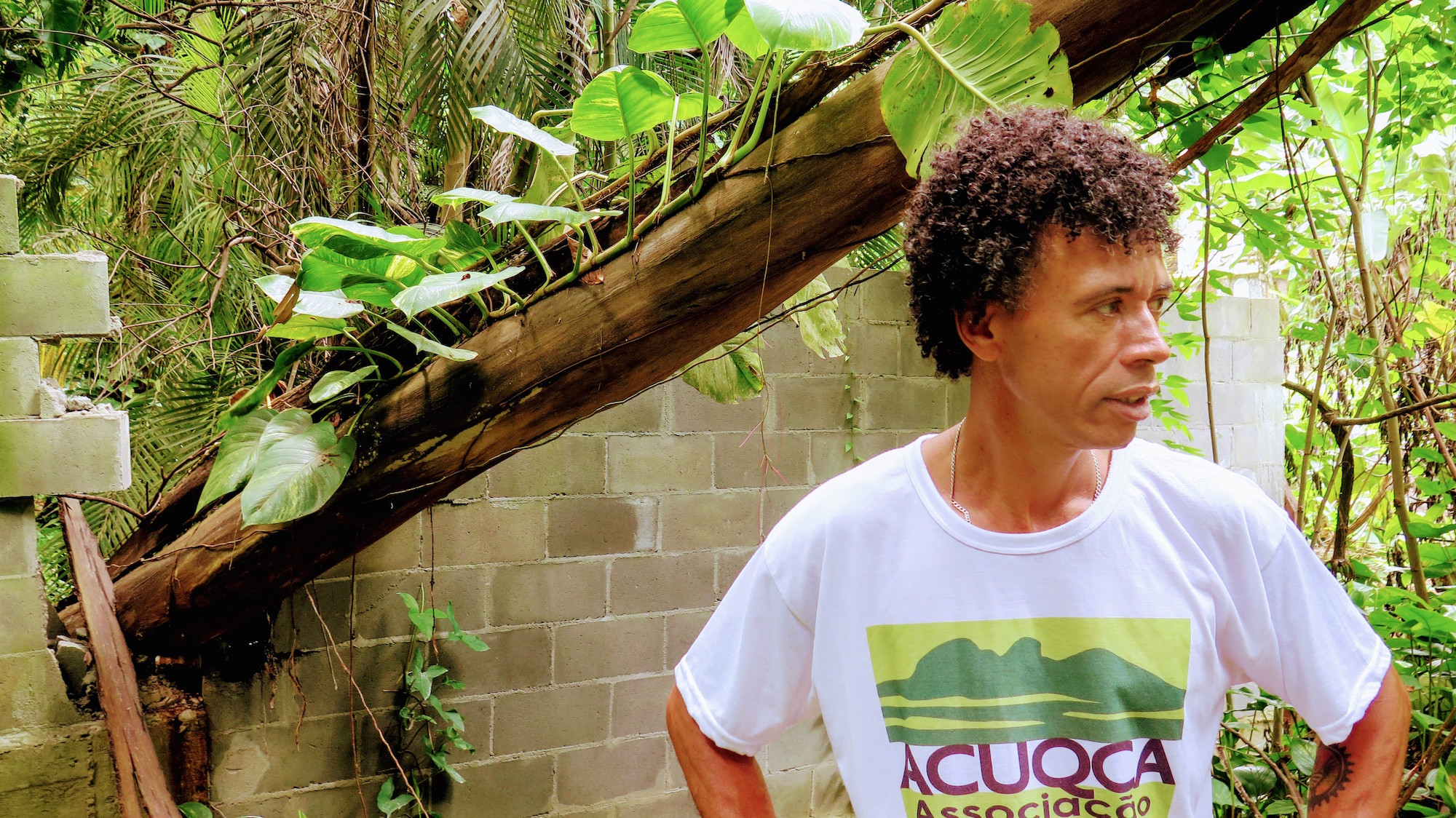 Adilson Almeida next to the wall constructed by the condominium, at a spot where a tree had fallen through