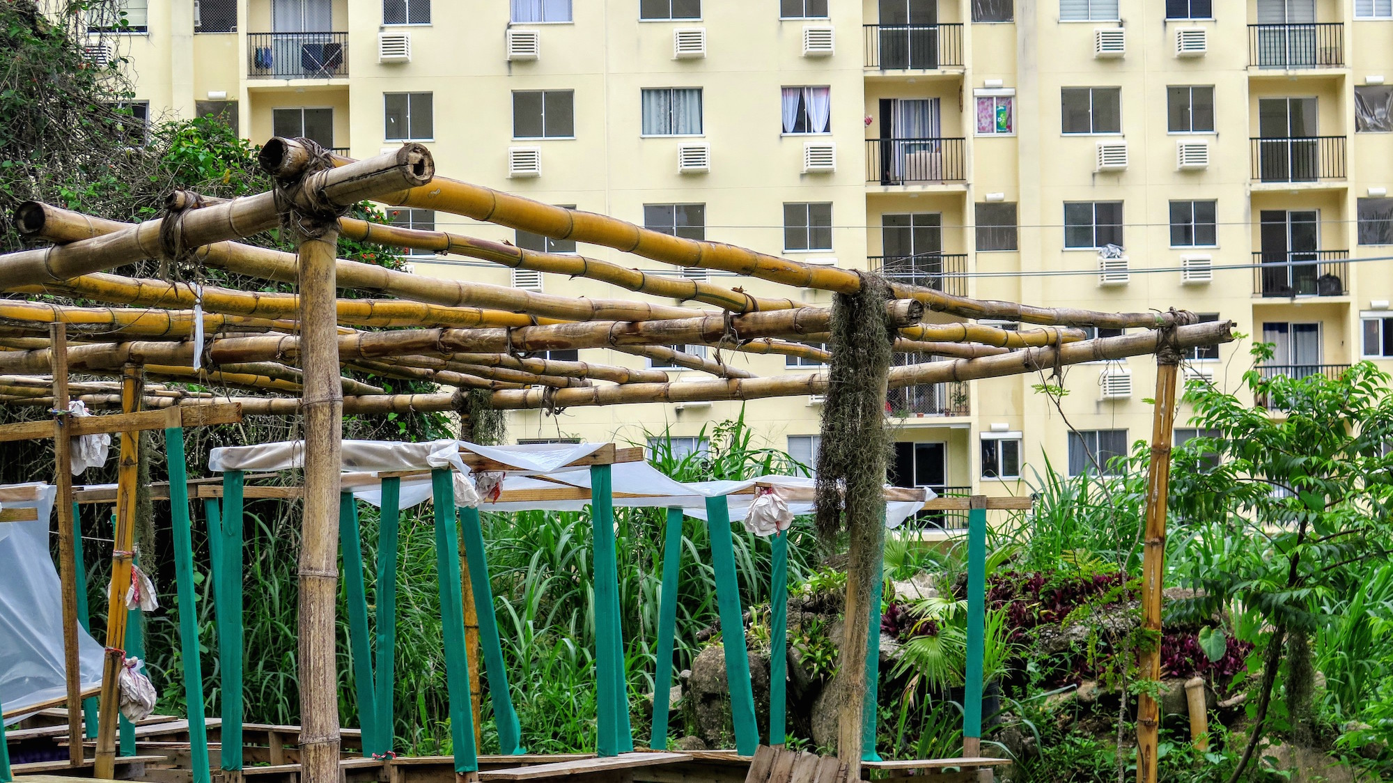 Condominium built on quilombo sacred lands in the background, as compared to bamboo structure utilized by the quilombo