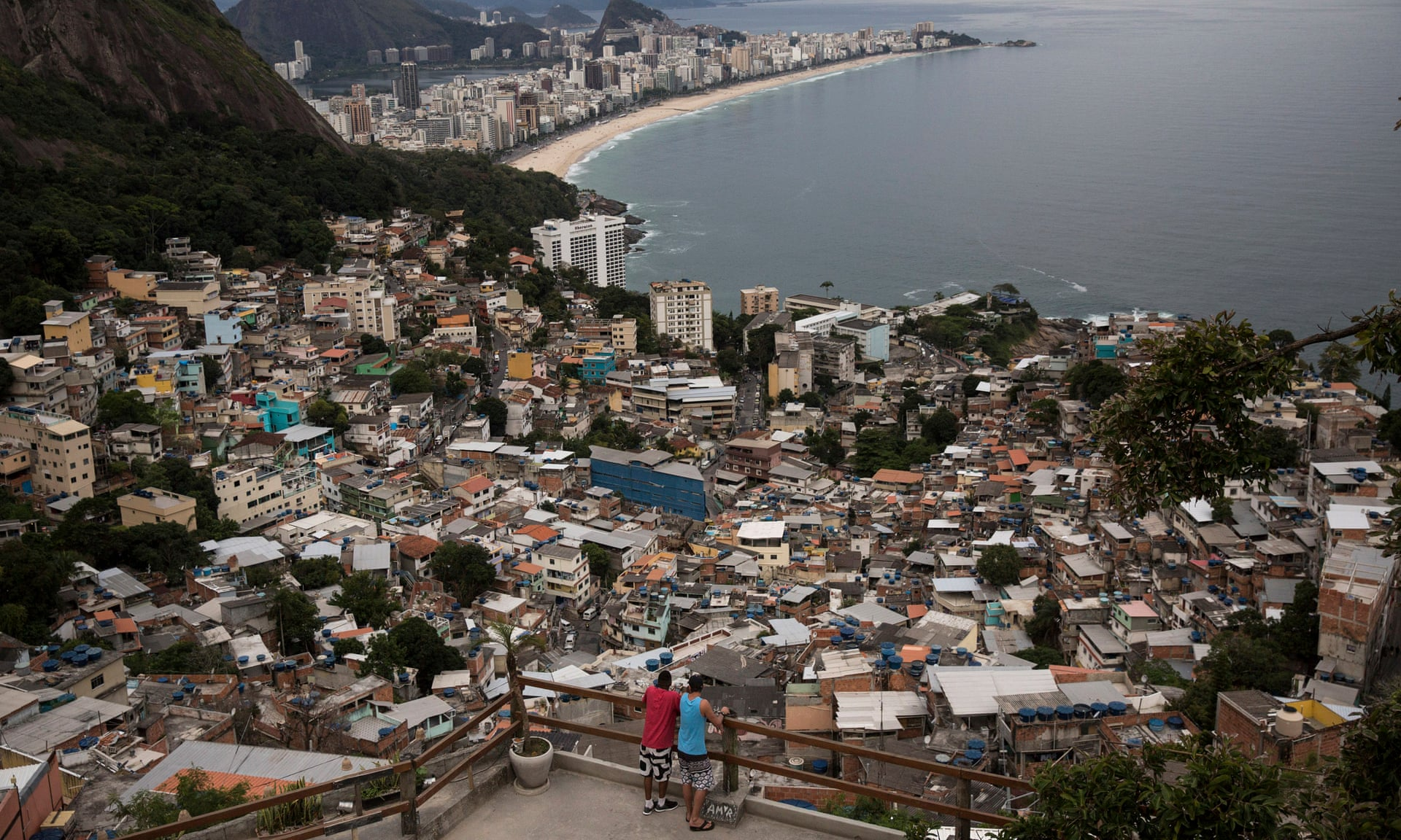 Men overlook the city from the Vidigal favela, in Rio de Janeiro, Brazil. Photograph: Renata Brito/AP