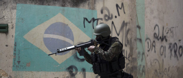There was a heavy military presence in certain favelas even prior to the 2018 military intervention. Here, a soldier takes aim during an operation in Barbante favela on Ilha do Governador, in Rio's North Zone, in November 2017. Photo: Leo Correa / AFP / Getty Images