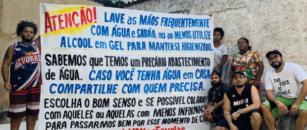 Members of Coletivo Papo Reto holding one of their banners with preventative information. Photo - Voz das Comunidades