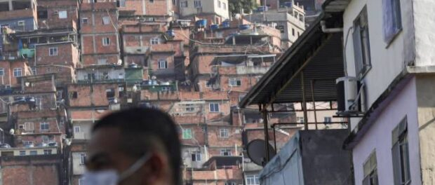 Man wearing a white mask with a favela as background. Photo by: Ricardo Moraes/Reuters