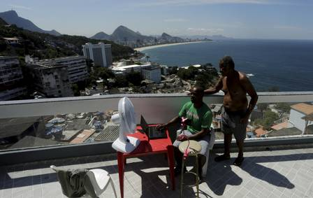 William de Paula and his father on their roof in Vidigal. Photo: Gabriel de Paiva / Agência O Globo