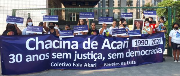 Mothers, fathers and relatives of victims of the state and favela activists hold a banner that reads 'Acari Massacre, 30 years without justice, without democracy' and street signs with the names of the 11 abducted youth in the massacre.