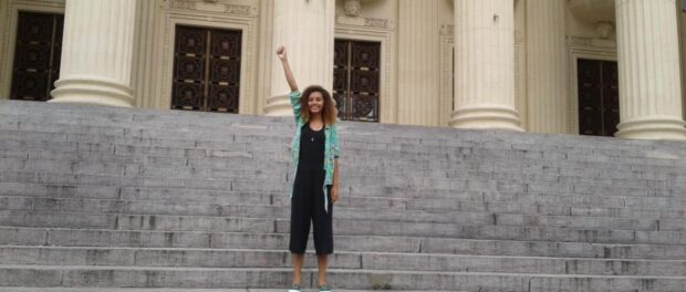 Thaisa Santos in front of ALERJ with her fist raised. Photo by: Thaisa Santos.